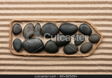Pointer made of rope with black stones stock photo, Pointer made of rope with black stones, lying on the striped sand by alekleks