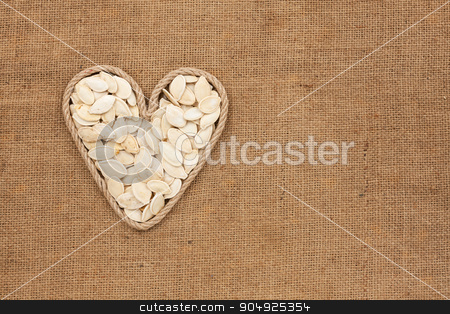 Heart made from rope with pumpkin seeds lying on sackcloth stock photo, Heart made from rope with pumpkin seeds lying on sackcloth, with space for text by alekleks