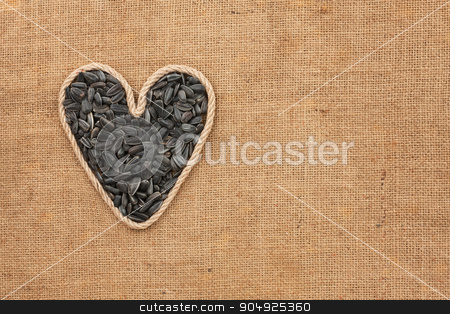 Heart made from rope with sunflower seeds lying on sackcloth stock photo, Heart made from rope with sunflower seeds lying on sackcloth, with space for text by alekleks