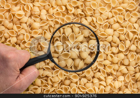 Human hand holding a magnifying glass over the pasta stock photo, Human hand holding a magnifying glass over the pasta can be used as background by alekleks