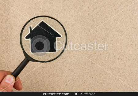 Hand with magnifying glass over the house in the sand stock photo, Hand with magnifying glass over the house in the sand, with space for your text by alekleks