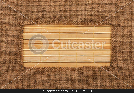 Frame made of burlap lying on a bamboo  mat stock photo, Frame made of burlap lying on a bamboo  mat, with space for your text by alekleks