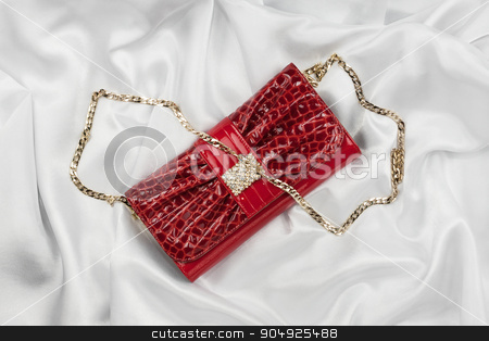 Red lacquer bag lying on a white silk stock photo, Red lacquer bag lying on a white silk, as background by alekleks