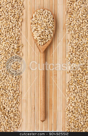 Wooden spoon with barley  stock photo, Wooden spoon with barley lying on a bamboo mat by alekleks