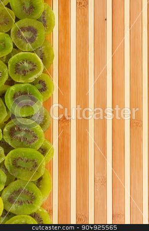 Dried kiwi lying on a bamboo mat  stock photo, Dried kiwi lying on a bamboo mat as background by alekleks