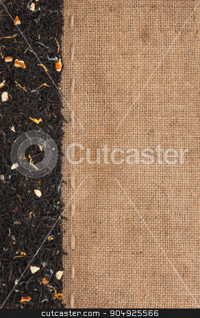 Black tea with additives lies on sackcloth stock photo, Black tea with additives lies on sackcloth, with space for text by alekleks