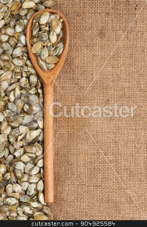 wooden spoon with pumpkin seeds stock photo, wooden spoon with pumpkin seeds, lies on the background burlap by alekleks