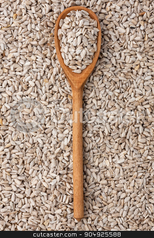wooden spoon with sunflower seeds  stock photo, wooden spoon with sunflower seeds is against the background of sunflower seeds by alekleks