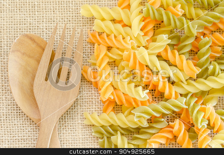 Three Colors Rotini Pasta stock photo, Three Colors Rotini Pasta with wooden spoon on sack background. by Miss. PENCHAN  PUMILA