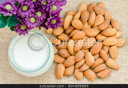 Almond with milk almond. stock photo, Almond with milk almond and violet flower on sack background. by Miss. PENCHAN  PUMILA