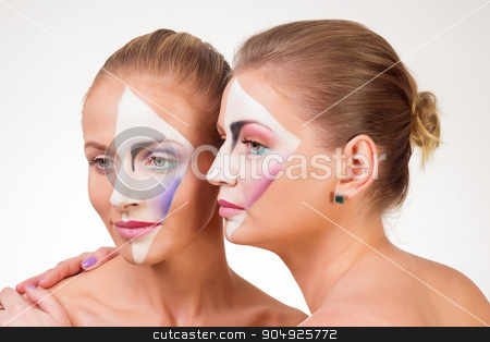 Portrait of two young girls with paint on his face stock photo, Portrait of two young girls with paint on his face. White background by ALEKSANDR
