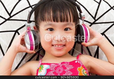 Chinese little girl on headphones holding mobile phone stock photo, Chinese little girl on headphones holding mobile phone sitting on sofa by Tan Kian Khoon