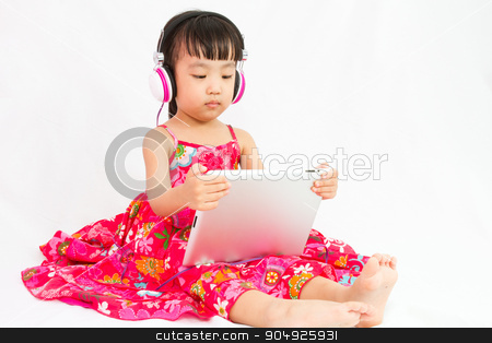 Chinese little girl on headphones holding tablet stock photo, Chinese little girl on headphones holding tablet in plain isolated white background. by Tan Kian Khoon