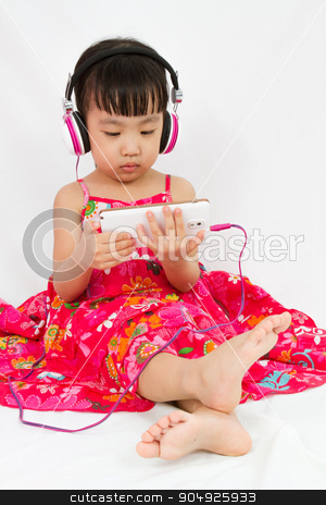 Chinese little girl on headphones holding mobile phone stock photo, Chinese little girl on headphones holding mobile phone in plain isolated white background. by Tan Kian Khoon