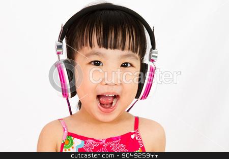 Chinese little girl on headphones stock photo, Chinese little girl on headphones with mouth open by Tan Kian Khoon