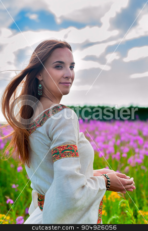 Beautiful woman relaxing on meadow with flowers stock photo, Attractive woman in traditional national dress relaxes with flowers by Aikon