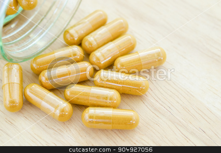 Herb capsule spilling out of a bottle. stock photo, Herb capsule spilling out of a bottle glass. by Miss. PENCHAN  PUMILA