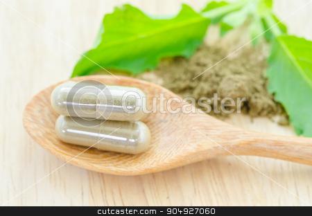 Herb capsule with green herbal leaf . stock photo, Herb capsule with green herbal leaf on wooden background. by Miss. PENCHAN  PUMILA
