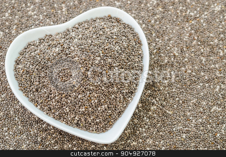 Chia seeds in white bow heart shape. stock photo, Chia seeds in white bow heart shape on chia seeds background. by Miss. PENCHAN  PUMILA