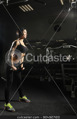 Brunette fitness girl perfect body in gym. doing triceps exercises stock photo, fitness woman doing triceps exercises in the gym. Brunette fitness girl in black sport wear with perfect body in gym exercising by Kopytin Georgy