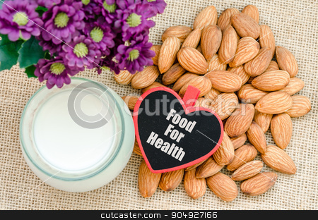 Almond with milk almond and food for health tag. stock photo, Almond with milk almond and food for health tag withviolet flower on wooden background. by Miss. PENCHAN  PUMILA