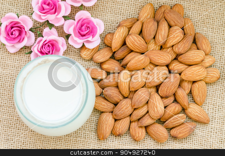 Almond and milk in glass with flower. stock photo, Almond and milk in glass with flower on sack background. by Miss. PENCHAN  PUMILA