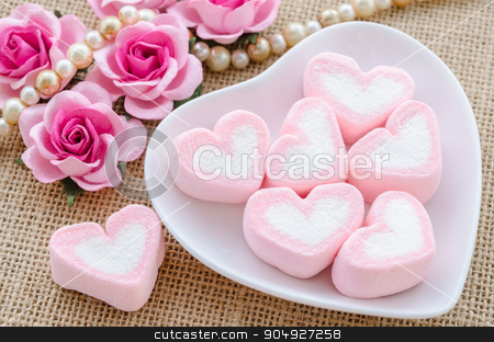 Pink heart marshmallows in white bowl. stock photo, Pink heart marshmallows in white bowl with rose flower on sack background. by Miss. PENCHAN  PUMILA