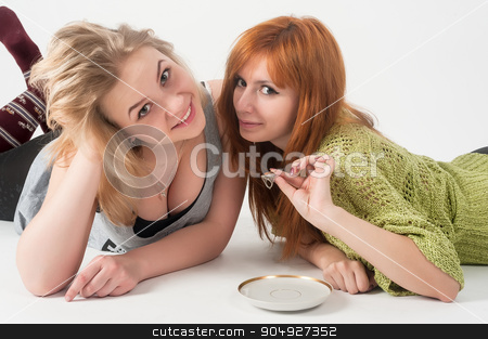 Two attractive girls lie and have fun stock photo, Beautiful girlfriends on floor guessing by means of a wedding ring over white background by Aikon