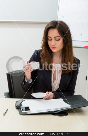 Business woman in the office. stock photo, Business woman in the office. Secretary drinking coffee in the workplace. by Denys