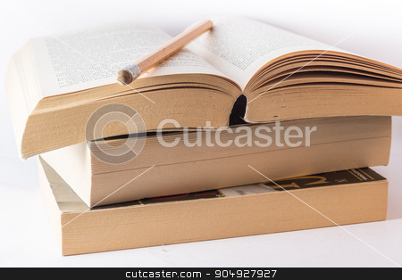 Books stack stock photo, Stack of old books and pencil on withe background. by Alfredo Steccanella