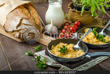Scrambled eggs with herbs and homemade bread stock photo, Scrambled eggs with herbs and homemade bread, on two frying pans by Peteer