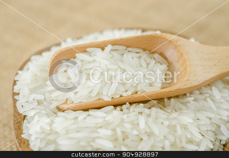 Raw rice in wooden bowl with wooden spoon. stock photo, Raw rice in wooden bowl with wooden spoon on sack background. by Miss. PENCHAN  PUMILA