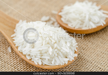 Raw rice in wooden spoon. stock photo, Raw rice in wooden spoon on sack background. by Miss. PENCHAN  PUMILA