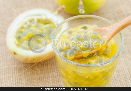 Passion fruit juice in glass with wooden spoon. stock photo, Passion fruit juice in glass with wooden spoon on sack background. by Miss. PENCHAN  PUMILA