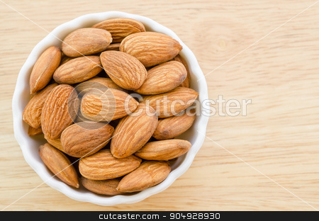 Almonds in white cup. stock photo, Almonds in white cup on wooden background. by Miss. PENCHAN  PUMILA