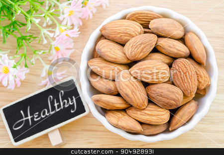 Almond and Health tag with flower. stock photo, Almond and Health tag with flower on wooden background. by Miss. PENCHAN  PUMILA