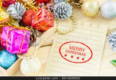 Banner and logo saying merry christmas. stock photo, Banner and logo saying merry christmas on brown paper with christmas decorations on wood background. by Miss. PENCHAN  PUMILA