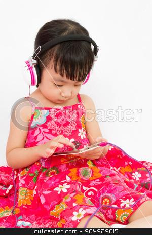 Chinese little girl on headphones holding mobile phone stock photo, Chinese little girl on headphones holding mobile phone in plain isolated white background. by Tan Kian Khoon