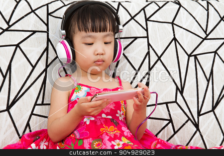 Chinese little girl on headphones holding mobile phone stock photo, Chinese little girl on headphones holding mobile phone sitting on sofa by Tan Kian Khoon
