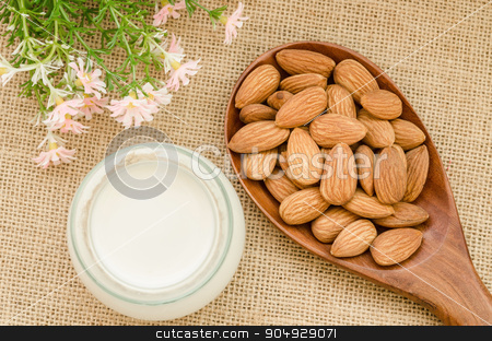 Almond milk with almond on a wooden spoon. stock photo, Almond milk with almond on a wooden spoon with flower on sack background. by Miss. PENCHAN  PUMILA