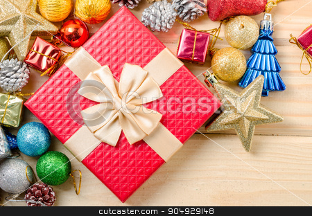 Red gift box and christmas decorations. stock photo, Red gift box and christmas decorations on wooden background. by Miss. PENCHAN  PUMILA