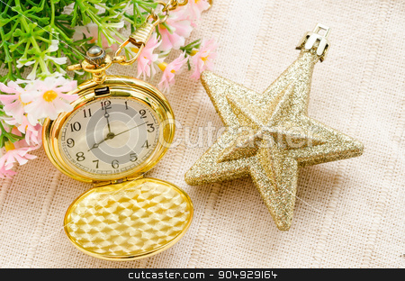 Gold pocket watch and gold star christmas with flower. stock photo, Gold pocket watch and gold star christmas with flower on fabric background. by Miss. PENCHAN  PUMILA