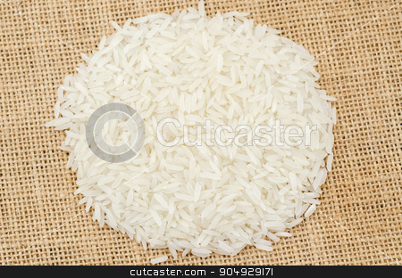 Heap of raw white rice. stock photo, Heap of raw white rice on sack background. by Miss. PENCHAN  PUMILA