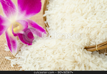 Raw rice with violet orchid flower. stock photo, Raw rice with violet orchid flower in weave basket on sack background. by Miss. PENCHAN  PUMILA