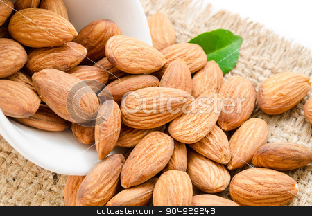 Almonds. stock photo, Almonds in white bowl with green leaf on sack. by Miss. PENCHAN  PUMILA