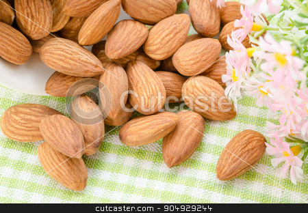 Sweet almonds in white cup with flower. stock photo, Sweet almonds in white cup with flower on sack background. by Miss. PENCHAN  PUMILA