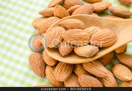 Almonds. stock photo, Almonds in wooden spoon on tablecloth. by Miss. PENCHAN  PUMILA