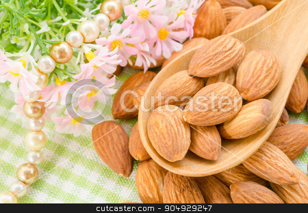 Almonds stock photo, Almonds in wooden spoon with flower on tablecloth. by Miss. PENCHAN  PUMILA