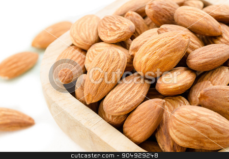 Almonds. stock photo, Almonds in wooden bowl on white background. by Miss. PENCHAN  PUMILA