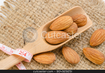Almond and measuring meter. stock photo, Almond and measuring meter on sack background. Diet concept. by Miss. PENCHAN  PUMILA